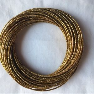 Jewelry - A stack of gold bangles
